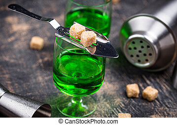 Glass of absinthe with cane sugar cubes on special spoon
