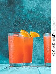 Glass of Alabama Slammer cocktail garnished with orange wedge
