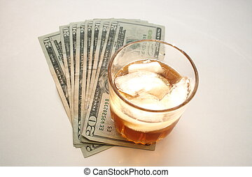 glass of alcohol with dollar bills