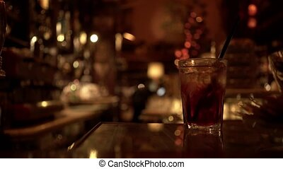Glass of alcoholic beverage on a bar table, blurred background