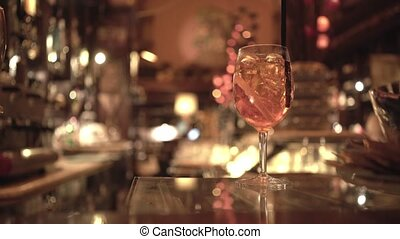 Glass of alcoholic cocktail on a bar table, blurred background