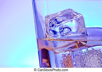 glass of alcoholic drink with ice on disco blue light