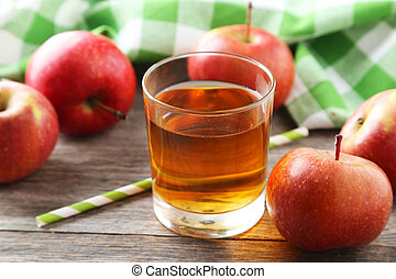 Glass of apple juice with apples on grey wooden background
