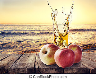 Glass of apple juice with apples on wooden table