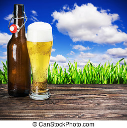 glass of beer and an empty bottle on the table
