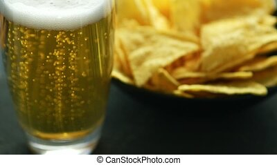 Glass of beer and nacho chips - Transparent glass of light...