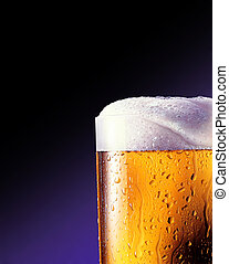 glass of beer close-up, with some foam coming out.