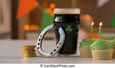 glass of beer, cupcakes, horseshoe and gold coins -...