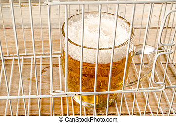 Glass of beer in a cage