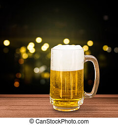 Glass of beer on bokeh background