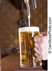 Glass of beer on pub, light through