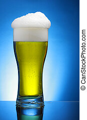 Glass of beer over blue background