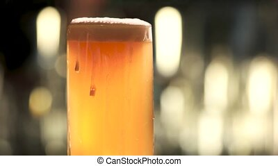 Glass of beer rotating and overflowing. Close up mug of light beer with foam dripping.