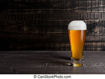 Glass of beer with frost on wood background
