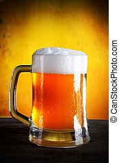 Glass of beer with gold background