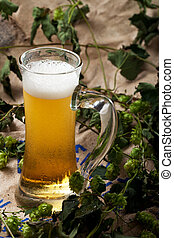 glass of beer with hop plants