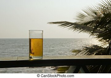 Glass of beer with sea background at the beach