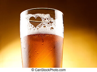 Glass of beer with the heart represented with froth close up...