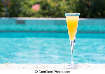 Glass of Bellini cocktail on the pool nosing at the tropical...