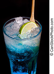 glass of blue cocktail with lime on black background