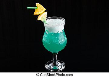 Glass of blue coctail with lemon on elegant dark black background.