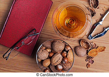Glass of brandy a book and nut selection