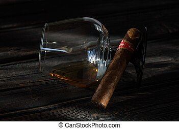 Glass of brandy and cuban cigar on an old wooden table.