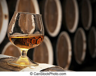 glass of brandy in the cellar is among the wooden barrels