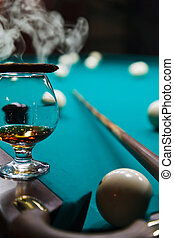 glass of brandy on the table for billiards and smoke cigars