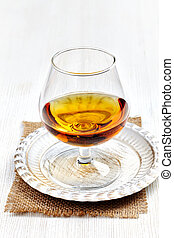 glass of brandy on white wooden table