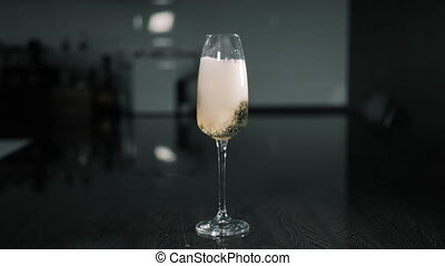Glass of champagne and falling strawberries slow motion on a dark background