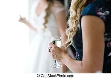 Glass of champagne in a guest hand during wedding reception, on background the bride
