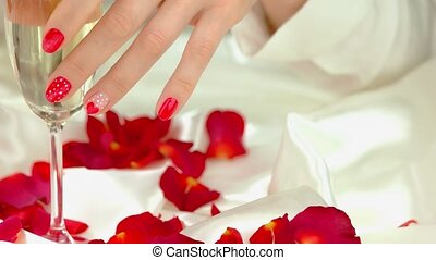 Glass of champagne in hands, red petals. Close up...