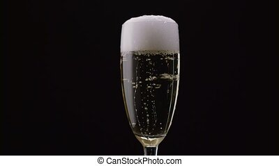 Glass of champagne with a rotating bubbles inside. Black background. Close up