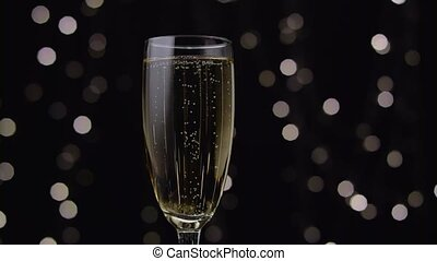 Glass of champagne with a rotating bubbles inside. Bokeh background