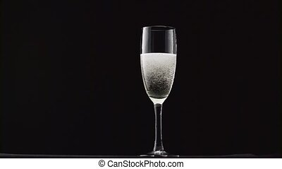 Glass of champagne with a rotating bubbles inside on a black background