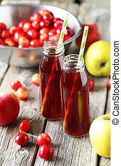 Glass of cherry juice with apple on grey wooden background