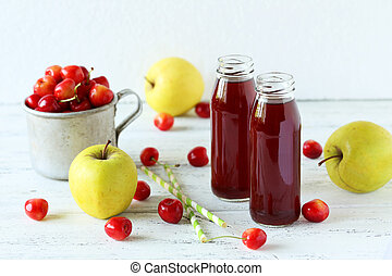 Glass of cherry juice with apple on white wooden background