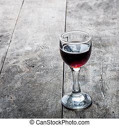 cherry liqueur - glass of cherry liqueur on wooden table