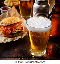 Glass of chilled beer with a hamburger