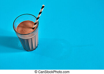 Glass of chocolate milk on blue background