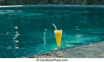 glass of cocktail is standing on the background of the pool...