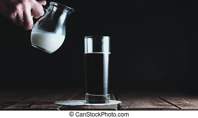 Glass of coffee being mixed with milk