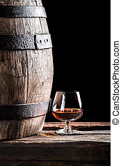 Glass of cognac and old oak barrel