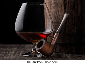 Glass of cognac brandy drink and vintage smoking pipe next to wooden barrel.