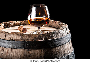 Glass of cognac on old wooden barrel