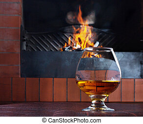 Glass of cognac on the old brick fireplace