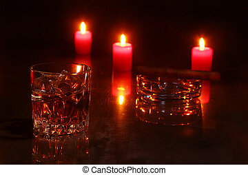 glass of cognac or whiskey, cigar and red candles on a wooden background. christmas decoration.