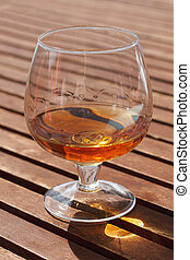 cognac - Glass of cognac standing on a wooden table in...