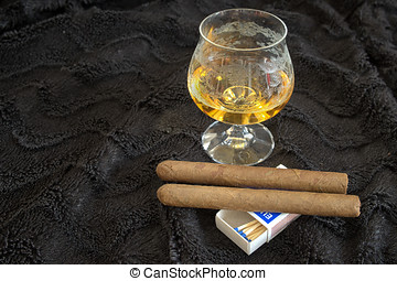 Glass of cognac with a cigar on a black velvet